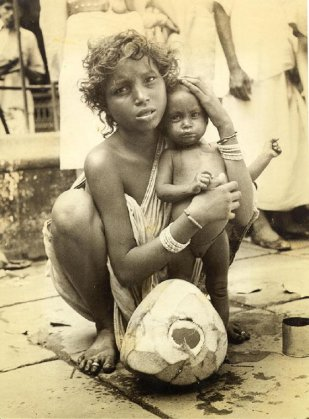 India has thousands of child bries. The unfortunate young waman shown here feeding the infant from thegiant coconat in foreground has been seen on Calcutta's streets day after day with he child. Her misery is more than typical thousands of India's unfortunates.