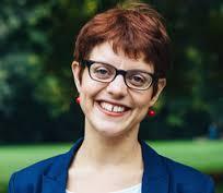 Porträtfoto. Hanna Parnow lacht fröhlich den Betrachter an. Sie hat kurze rote Haare, eine dunkel gerahmte Brille und eine Lücke zwischen den beiden oberen Schneidezähnen. Sie trägt ein weißes Shirt unter ihrem blauen Blazer, der an den Schultern zu erkennen ist.