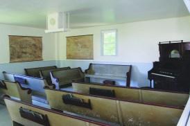 Modern side with church pews and pump organ.