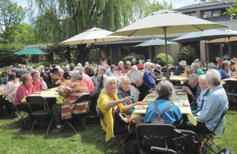 Friends House residents and guests gather for an outdoor luncheon on the Green.