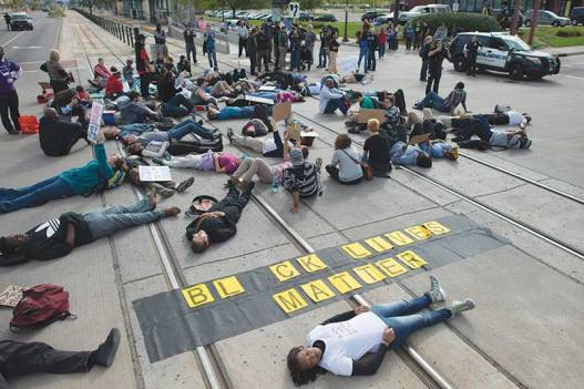 On September 20, 2015, around 100 protesters blocked the light rail line in St. Paul, Minn., to protest the treatment of Marcus Abrams by St. Paul police. Abrams, who is 17 and has autism, was violently arrested by Metro Transit Police on August 31, 2015. During his arrest he suffered a split lip and multiple seizures. (c) Fibonacci Blue. WIkimedia Commons.