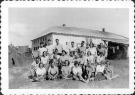 Workcampers; schoolhouse in background; tent on left.