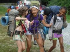 Campers laugh with a counselor as they head out for their three-day overnight backpacking trip.