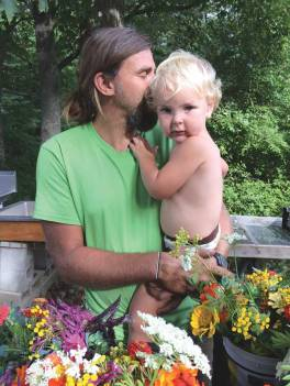 The author holding a child among flowers.