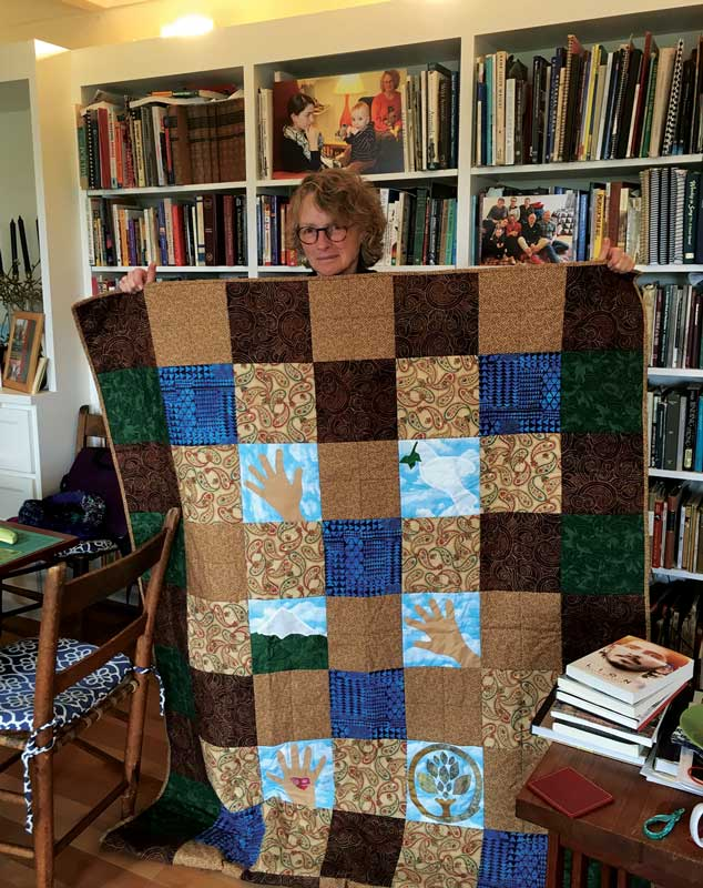 Local support committee member and quilter Jane Snyder proudly displays one of her quilts.