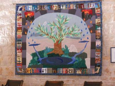 Peace and Justice Quilt at the Ramallah Friends Meetinghouse showing the fire of strife turning into rain drops that flow into the River of Justice that flows past thee Olive Tree which is the symbol of Palestinian steadfastness.