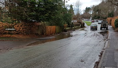 Puddle blocks one side of road to school