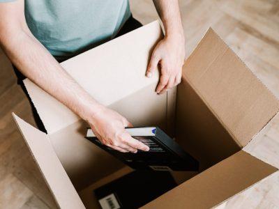 crop-man-packing-books-in-carton-box-4498123