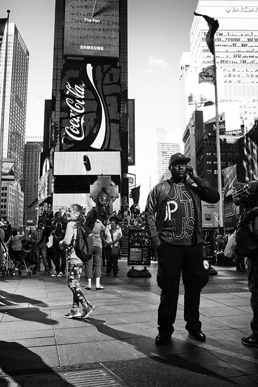 Street photographer friso kooijman fotograaf Amsterdam Nederland Netherlands zwart wit black white straatfotograaf New York Zaandam big man times square girl playing wondering advertisement coca cola