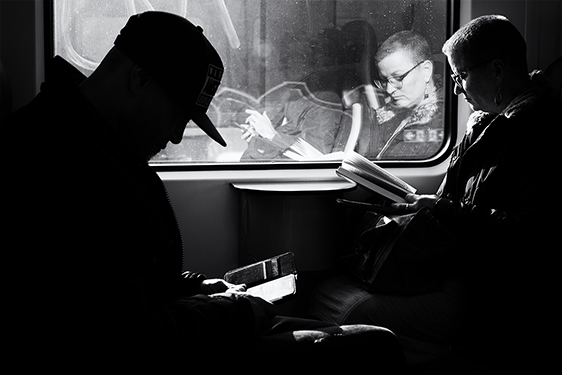 Street photographer friso kooijman fotograaf Amsterdam Nederland Netherlands zwart wit black white fotograaf train reading telephone book reflection