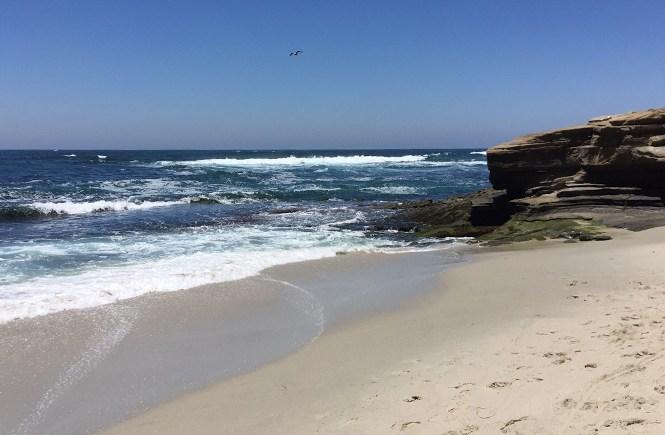 Ocean waves meet the sand and rocks.