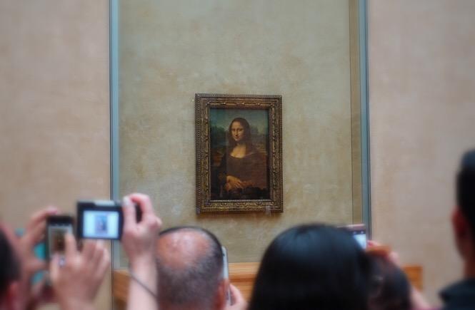 Photo of a crowd gathering around the Mona Lisa.