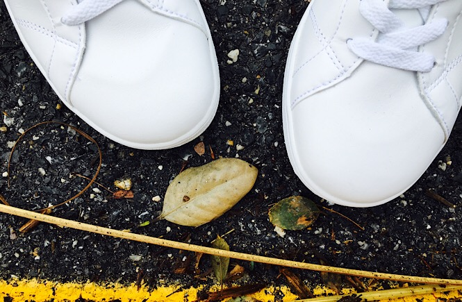 A pair of white sneakers in front of twigs on asphalt next to a yellow curb.
