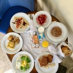 Photo of multiple plates of breakfast food on a table.