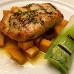 Salmon on a bed of sweet potatoes with a large leek on the side.