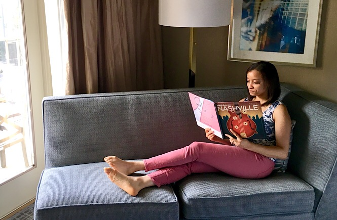 Me sitting on a sofa reading a guide book to Nashville, TN.