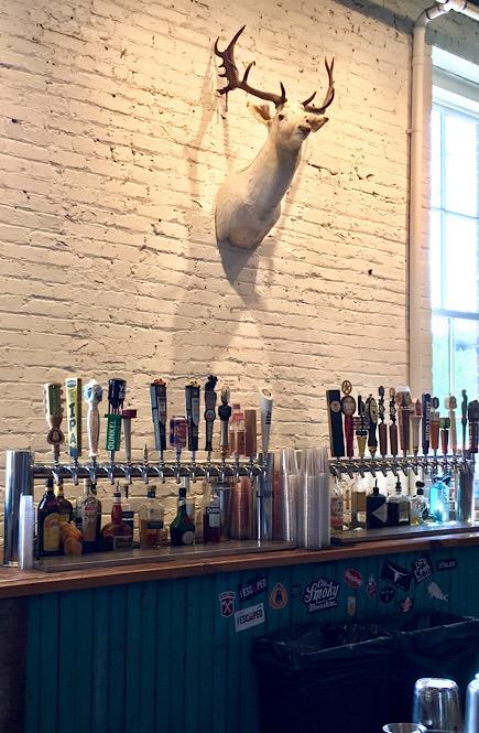 A deer bust hangs behind the bar tap.