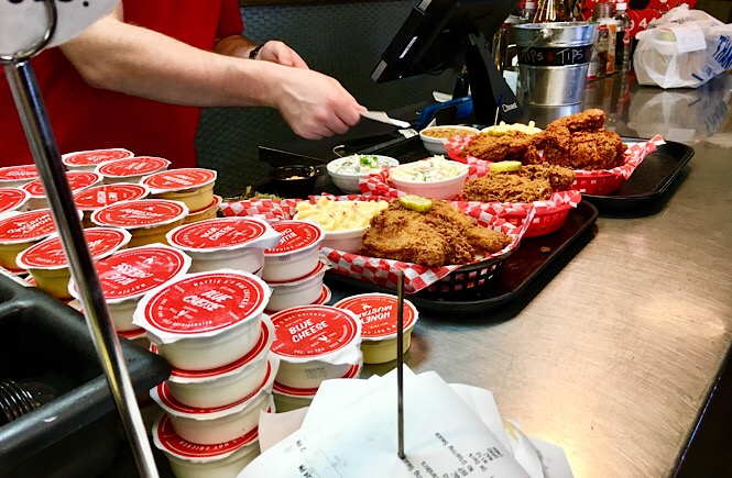 Busy restaurant counter with condiments and hot chicken platters.
