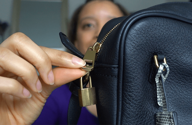 Photo of me holding a brass lock on a compact black leather bag. Frolic & Courage.