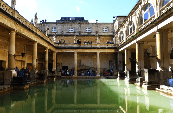 Photo of green water and the ancient pillars of the roman baths.