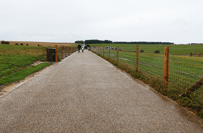 Photo of a long, paved path in the middle of farmland.