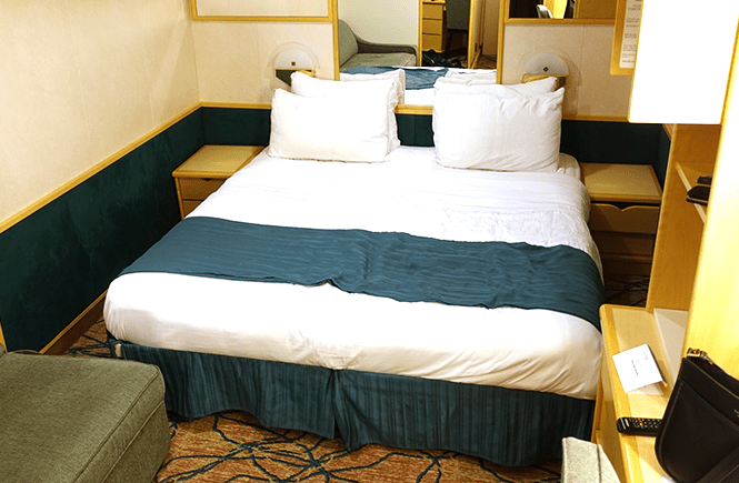 Photo of a king sized bed in a Royal Caribbean interior cabin stateroom. Frolic & Courage.