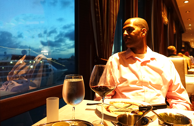 Photo of Hun staring out the window at Chops Grille on Royal Caribbean's Enchantment of the Seas. Frolic & Courage.