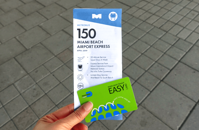 Photo of me holding a Miami Airport Express Route 150 pamphlet and an Easy Pass card. Frolic & Courage.