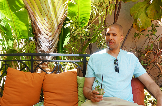 Photo of Kevin sitting on an outdoor sofa holding a fresh mojito at Ball & Chain in Little Havana.