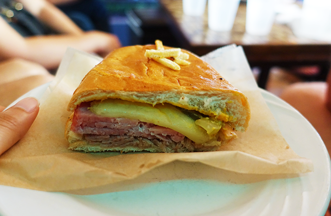 Closeup photo of my holding a plate with a half-sliced Cuban sandwich.