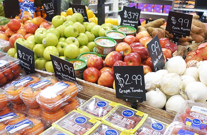 Photo of fresh produce displayed next to price signage at a grocery store.