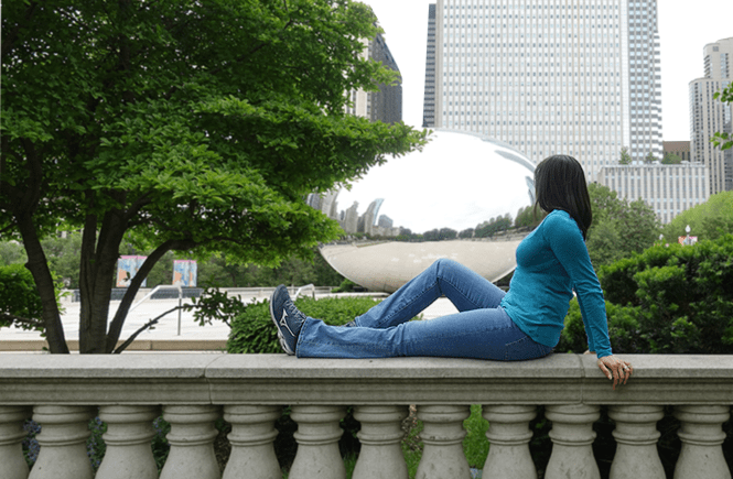 Photo of a woman looking at the Big Bean from on top of a balcony at Millennium Park in Chicago, Illinois.