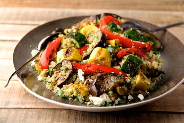 Mediterranean Quinoa and Grilled Vegetable Salad on a platter with gray border on a rough wood table taken from far away