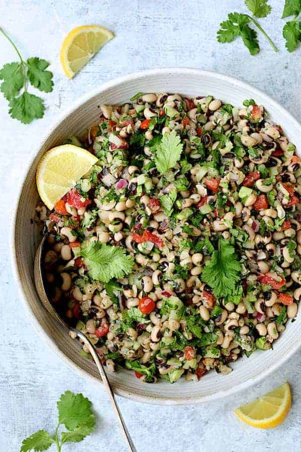 Spicy Black-Eyed Pea Salad - Overhead shot of salad in white bowl garnished with cilantro and lemon wedges
