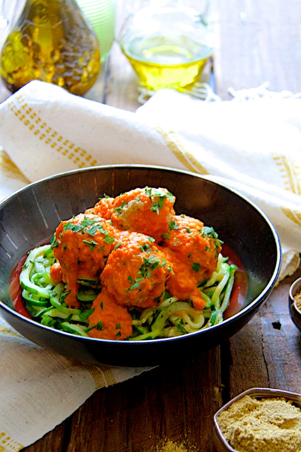 Chicken Meatballs with Roasted Red Pepper Chickpea Sauce and Zucchini Noodles - In black bowl on white and yellow striped towel on wood surface with spices