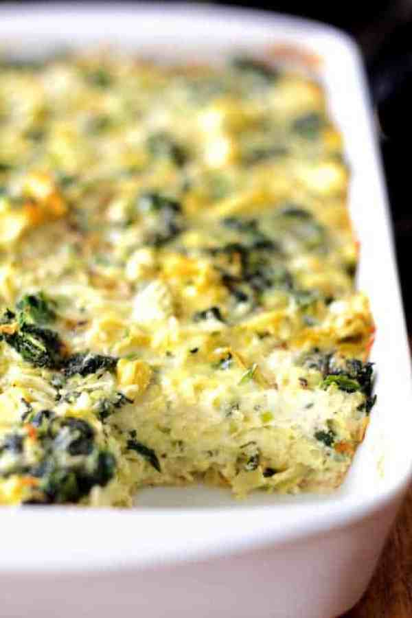 Spinach Artichoke Squares - Shot of squares in white baking dish with a piece removed