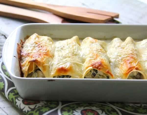 Chicken, Spinach and Artichoke Cannelloni - On green printed napkin in white baking dish with wooden utensils in the background