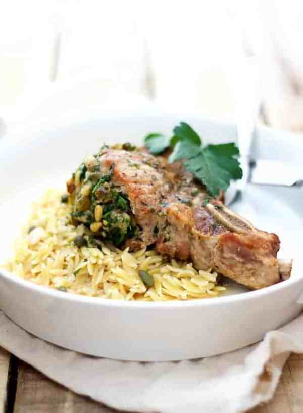 Sicilian Stuffed Pork Chops with White Wine Caper Sauce - Close-up shot of dish on white plate with orzo garnished with parsley