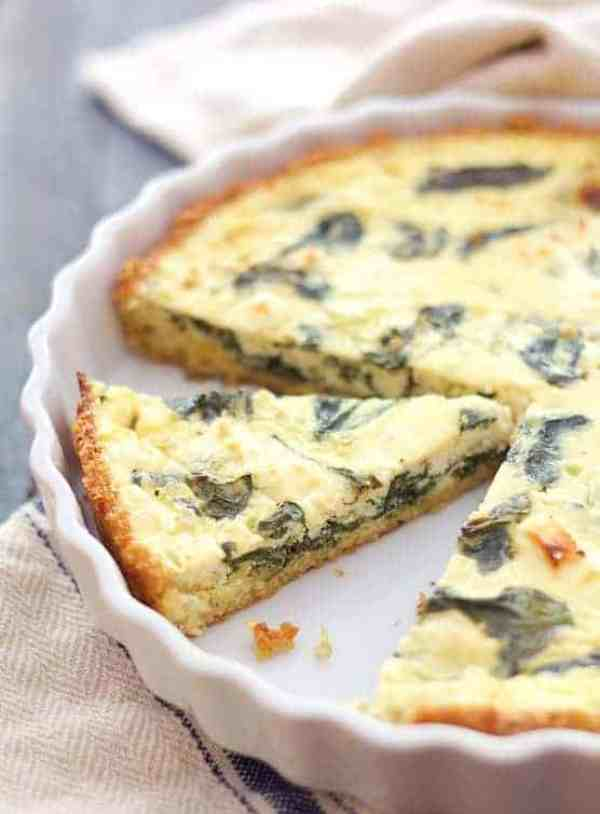 Spinach and Feta Quiche with Quinoa Crust - Shot of quiche in white baking dish with two slices removed