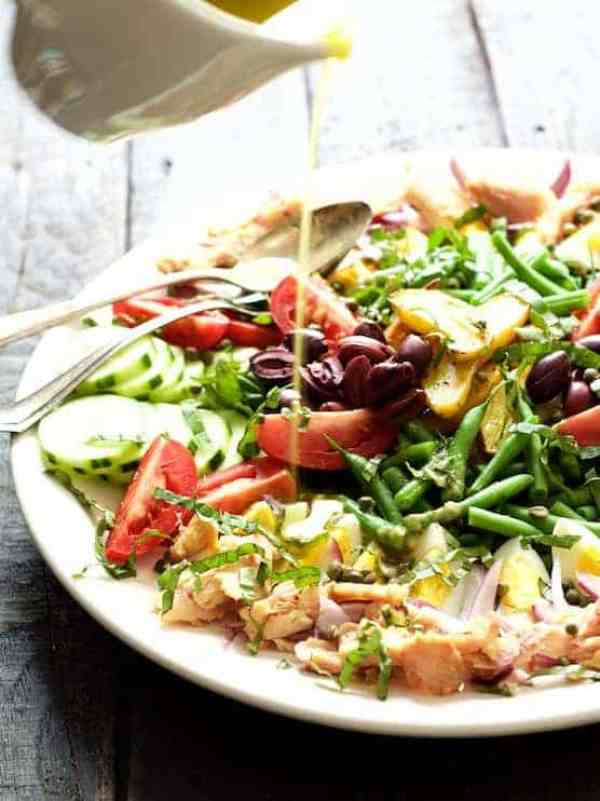 Salade Nicoise - Salad being drizzled with vinaigrette from small white pitcher