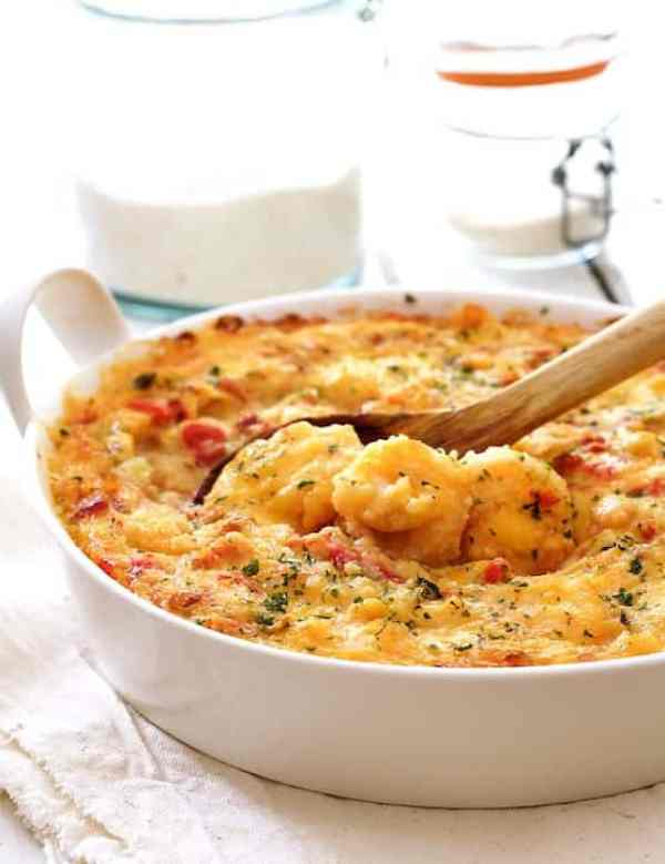 Spicy Shrimp and Grits Casserole with Gouda Cheese - Hero shot in white baking dish with some of the shrimp being scooped up with wooden spoon