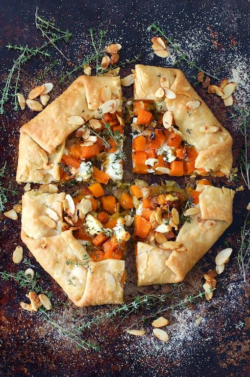Butternut Squash Leek and Goat Cheese Galette - Overhead shot of galette on dark background garnished with thyme sprigs and toasted almonds