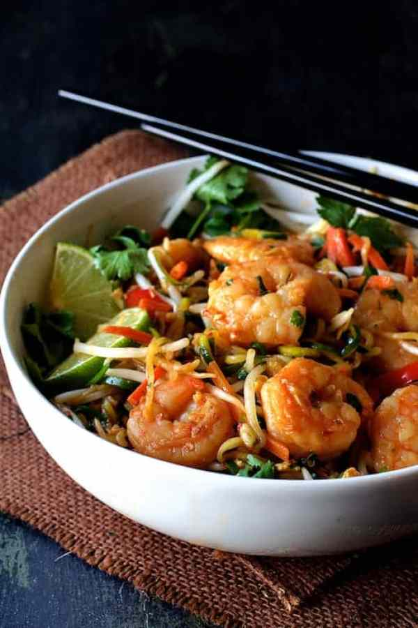 Shrimp Pad Thai with Zucchini Noodles - Straight-on hero shot of dish in white bowl on brown burlap with black chopsticks