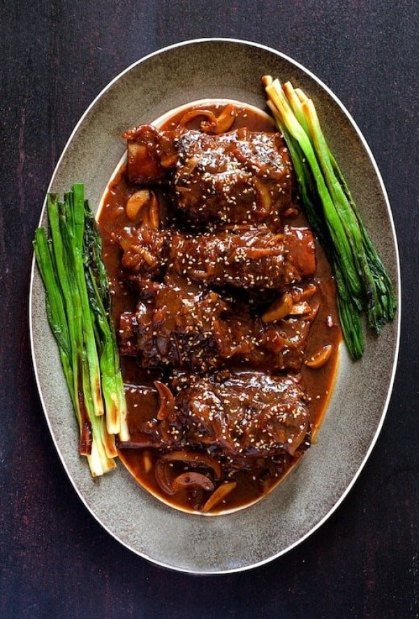 Korean Braised Beef Short Ribs - Overhead shot of ribs on gray-rimmed platter garnished with scallions