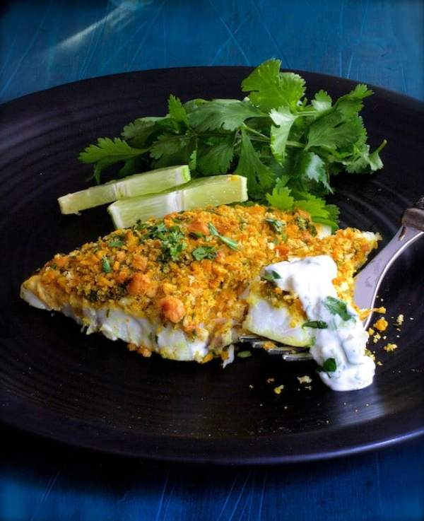 Curried Chickpea Encrusted Fish with Jalapeno Lime Tartar Sauce - Close-up shot of dish on black plate garnished with cilantro and lime wedges