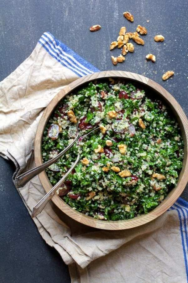 Quinoa and Kale Salad with Red Grapes, Walnuts and Honey - Lemon Dressing - Overhead shot of salad on blue striped towel on background with walnuts scattered about