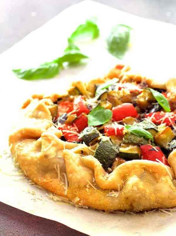 Mediterranean Roasted Vegetable Galette - Close-up straight on shot of galette on parchment paper garnished with fresh basil