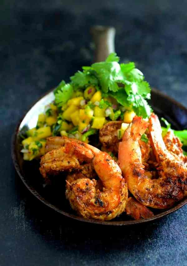 Grilled Citrus Chili Shrimp with Mango Pineapple Salsa - Hero shot of shrimp on cast iron pan garnished with fresh cilantro