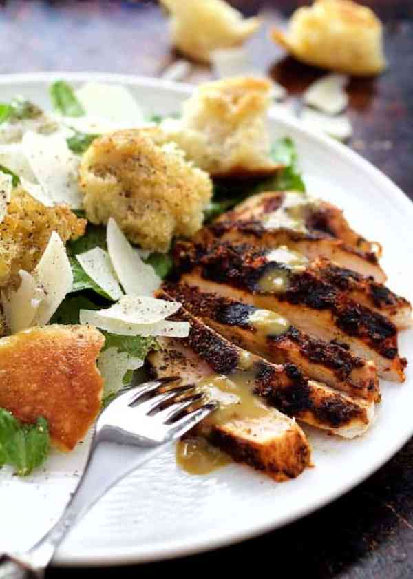 Blackened Chicken Caesar Salad with Sourdough Croutons - Shot of salad on white plate with fork ready to take a piece