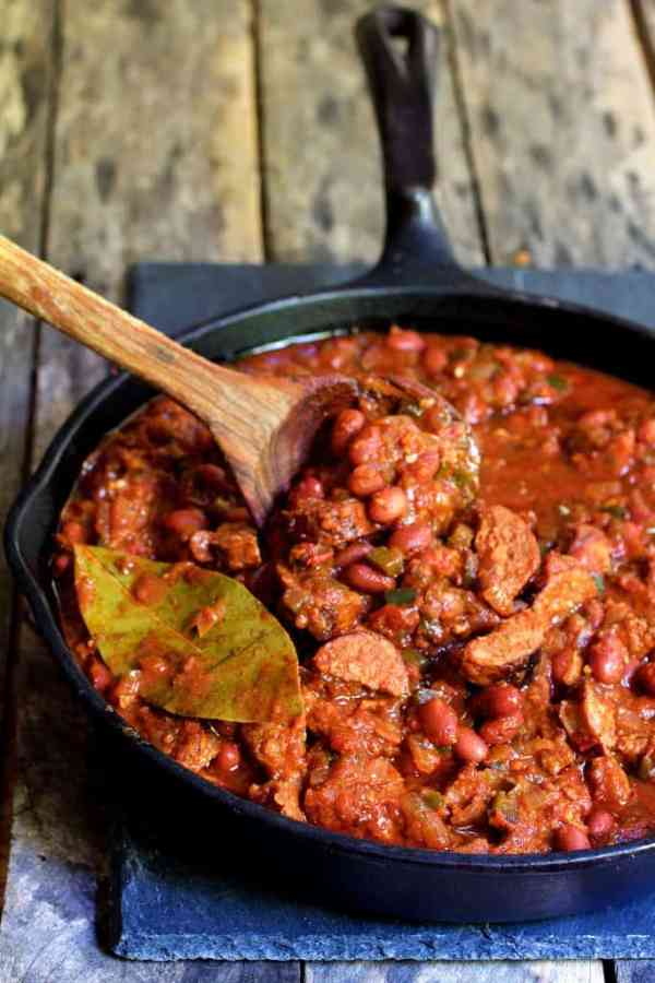 Red Beans and Rice with Chorizo and Bell Pepper Saute being stirred in cast iron skillet with wooden spoon